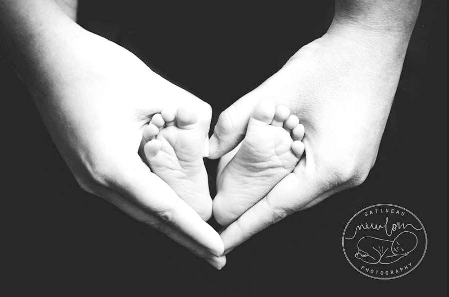 classic black and white newborn photo baby toes feet in mom dad hands matte edit high contrast