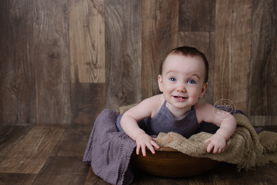 baby-photos-milestone-10-months-smiling-sitting-barnwood-floor-upcycled-purple-knit-sweater-sitter-romper-wood-bowl-burlap-layer-lavender-dolly-priss-wrap