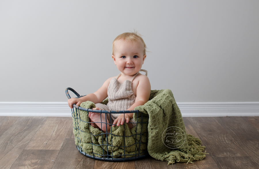 12-months-baby-photos-vintage-blue-wire-mesh-basket-barnwood-green-blanket-daddymackhats-romper